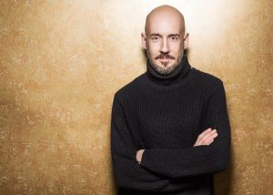 a bald person standing against the wall wearing a sweater