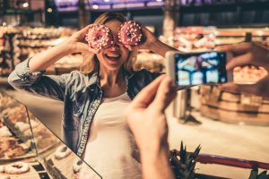 a woman taking a photo with donuts as glasses