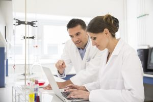 two lab operators working with data in a lab wearing white coats